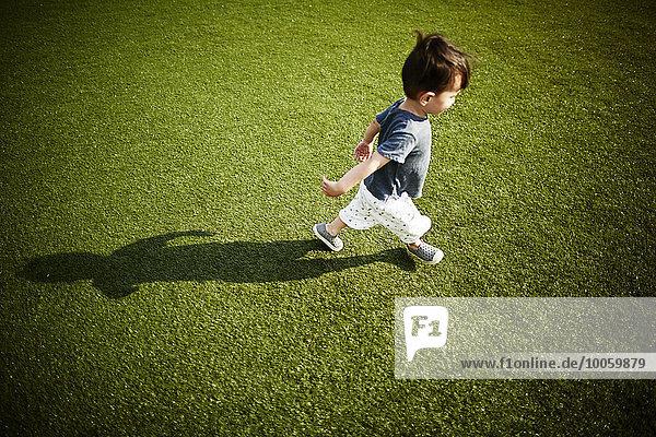 Junge mit Schatten  der über das Gras läuft