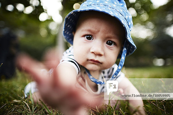 Close up of baby boy reaching out towards camera