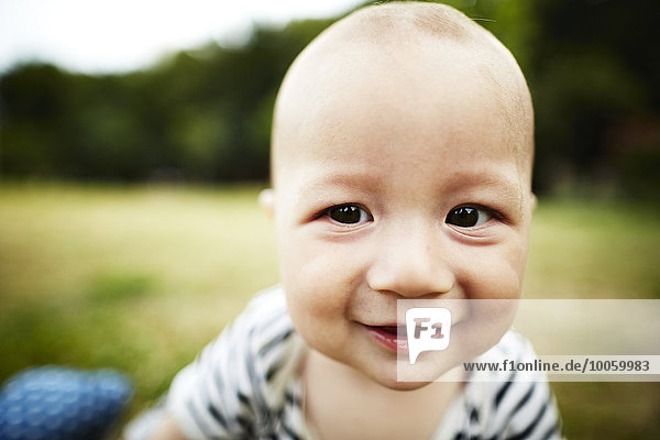 Close up portrait of baby boy smiling at camera