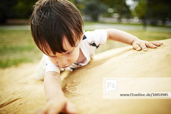 Nahaufnahme eines Jungen beim Klettern auf einen Sandfelsen