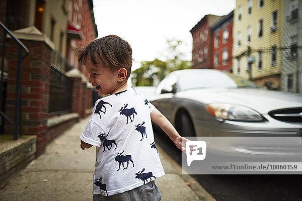 Junge rennt die Straße hinunter