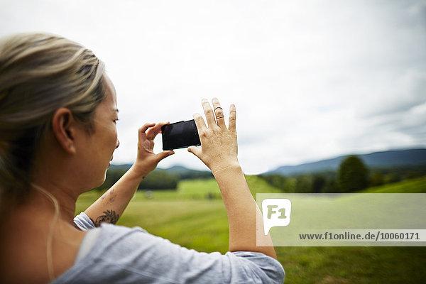 Frau beim Fotografieren auf dem Smartphone der ländlichen Feldlandschaft