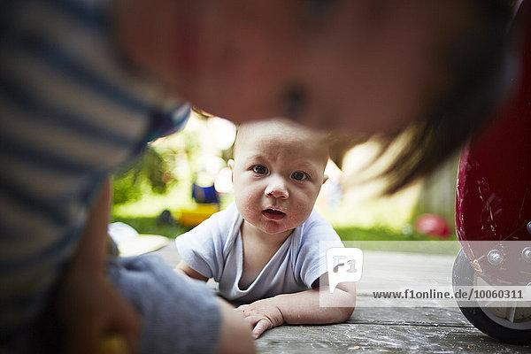 Porträt eines Jungen im Liegen mit Blick auf die Kamera  wobei der ältere Bruder im Vordergrund steht.