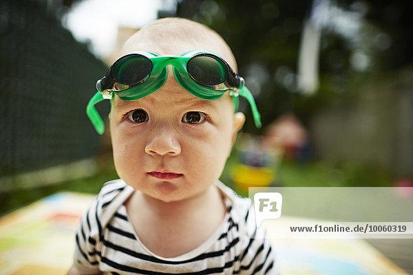 Nahaufnahme Porträt eines kleinen Jungen  der mit einer Schwimmbrille auf die Kamera schaut Nahaufnahme Porträt eines kleinen Jungen, der mit einer Schwimmbrille auf die Kamera schaut