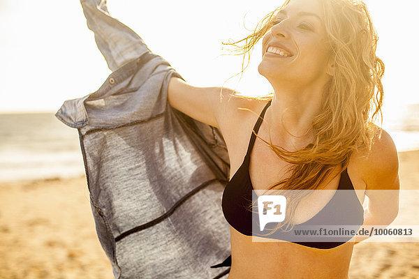 Frau beim Anziehen des Shirts am Strand