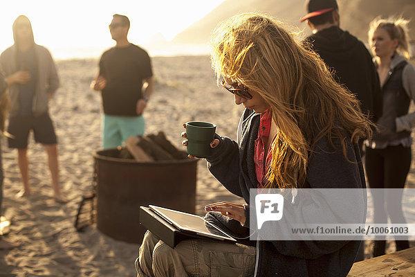 Frau mit digitalem Tablett am Strand  Freunde im Hintergrund