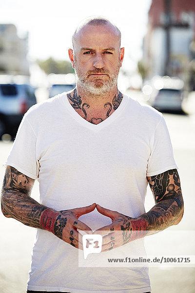 Reifer Mann mit Tattoos an Armen und Hals