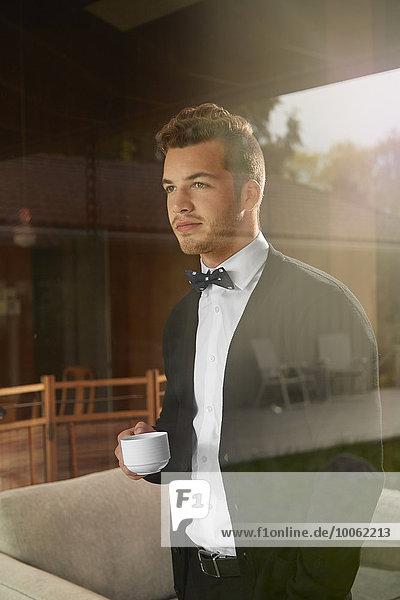 Schuss durch das Fenster des Mannes  der aus dem Blickfeld steht und eine Tasse Kaffee hält.