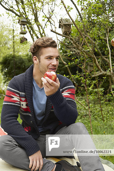 Portrait of smiling man sitting in garden eating an apple