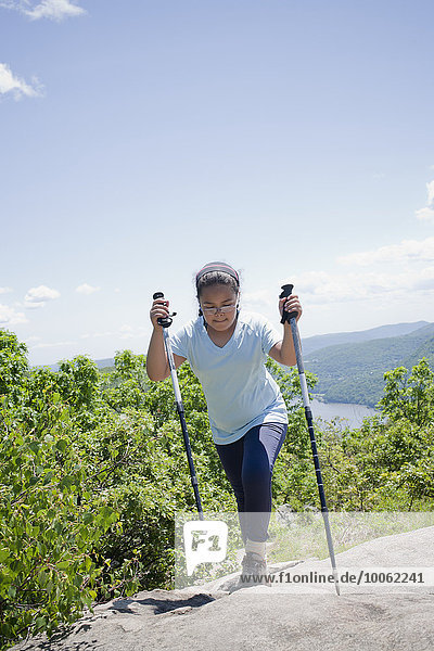 Young girl hiking up hilly landscape