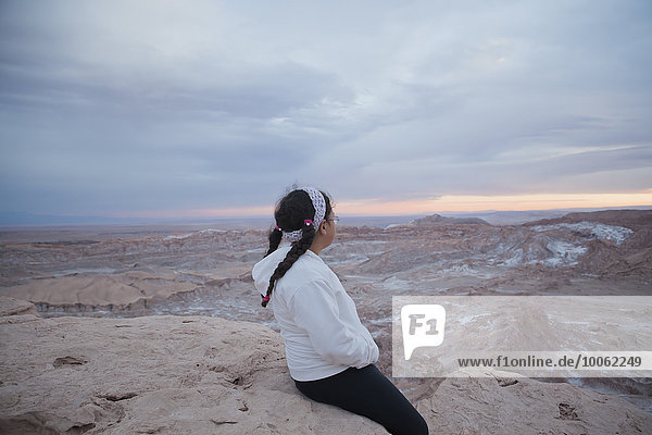 Young girl sitting on rock looking at view  Valley of the Moon  San Pedro. Atacama. Chile