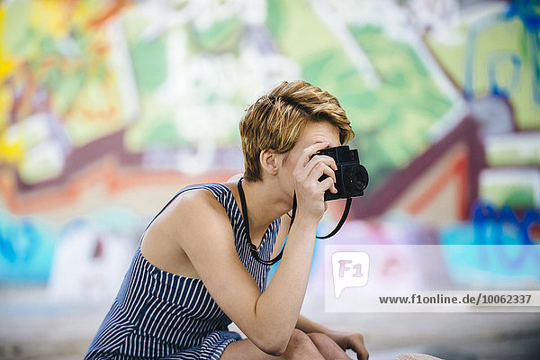 Stylish teenage girl photographing with camera in front of graffiti wall