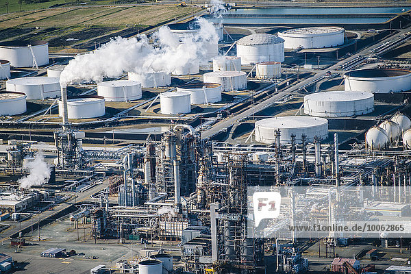 Reihen von Weißöllagertanks und Rauchschlot in der Ölraffinerie