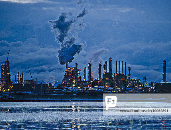 View of coastal oil refinery and smoke stacks at dusk