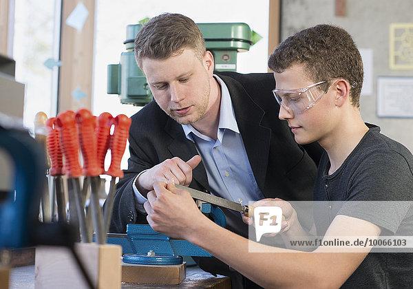 Lehrer mit Schüler an einem Werkstück