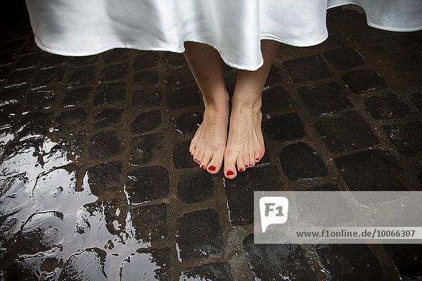 Braut steht barfuß auf nassen Sanpietrini Steinen in Rom  Italien  Europa