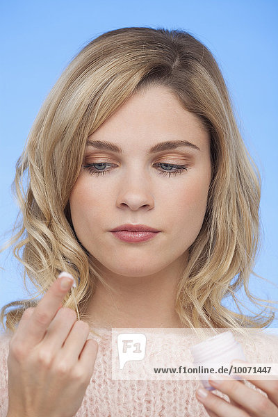 Close-up of a woman holding moisturizer cream