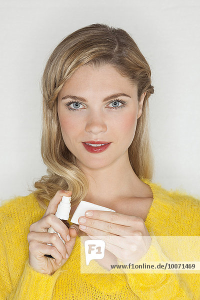 Close-up of a beautiful woman holding essential oil