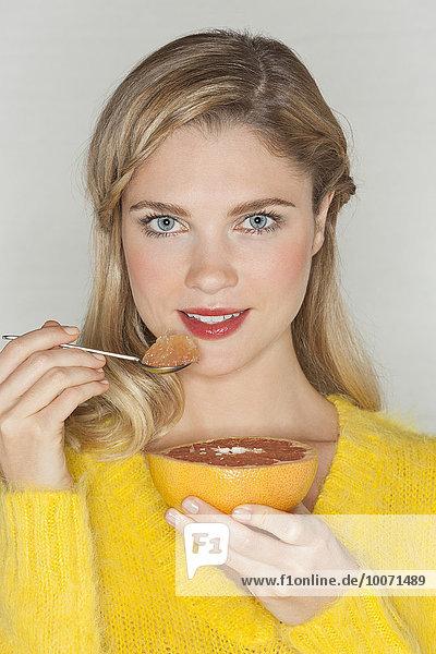 Porträt einer schönen Frau beim Grapefruitessen
