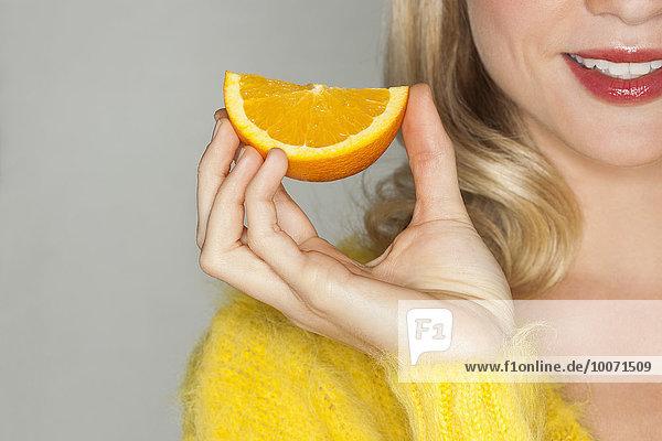 Nahaufnahme einer schönen Frau mit einer Orangenscheibe