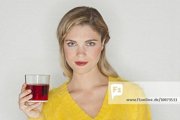 Porträt einer schönen Frau mit einem Glas Saft