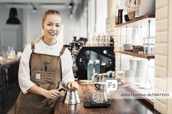 Porträt einer glücklichen Barista an der Theke im Coffee Shop