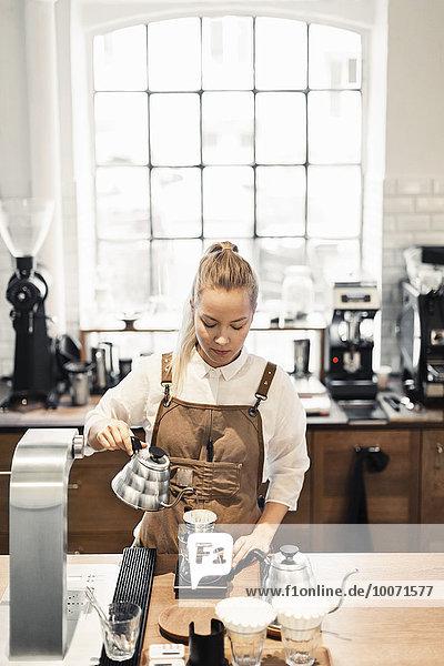 Weibliche Barista bei der Kaffeezubereitung am Cafe Counter