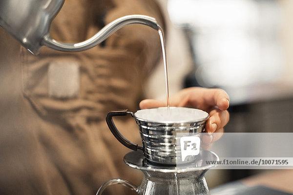 Abgeschnittenes Bild eines Barista  der Wasser in eine Kaffeetasse im Cafe gießt.