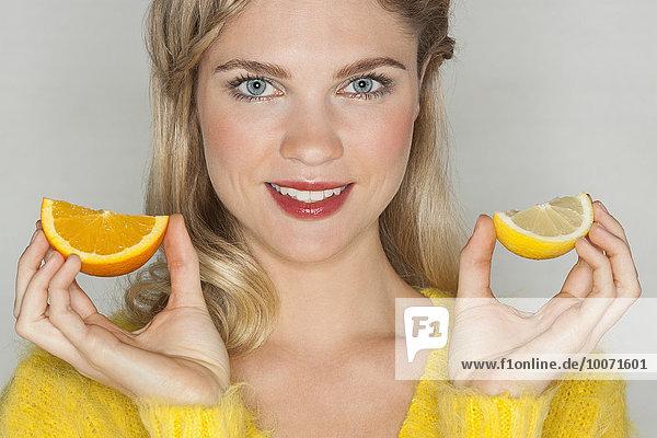 Porträt einer schönen Frau mit Orangenscheiben und Lächeln