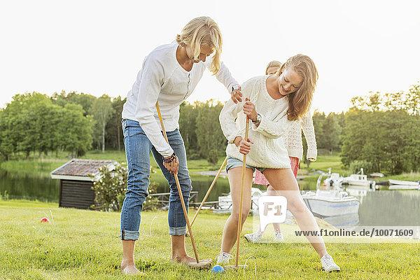 Fröhliche Freunde spielen Krocket auf dem Feld am See gegen klaren Himmel