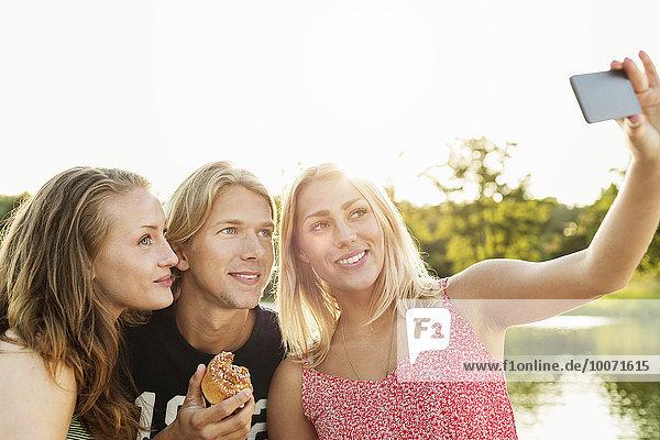 Fröhliche Freunde beim Frühstück am See bei klarem Himmel