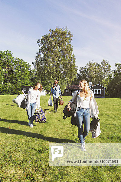 Freunde mit Taschen und Picknickkorb auf dem Spielfeld