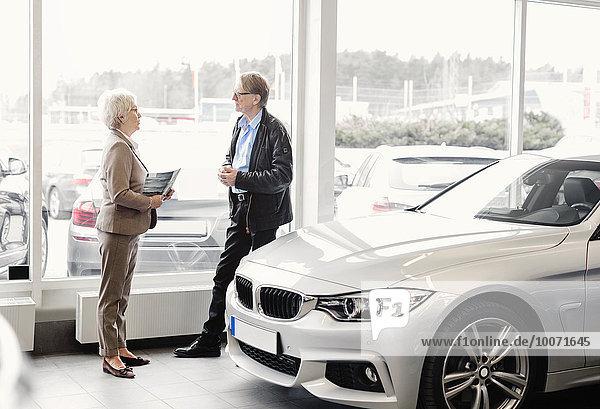Seitenansicht der Seniorin im Gespräch mit dem Mann im Autohaus