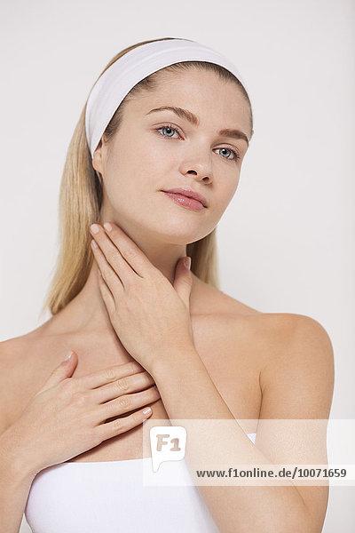 Beautiful woman applying moisturizer on her neck