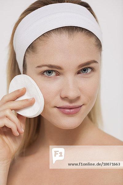 Frau putzt ihr Gesicht mit einem Wattebausch