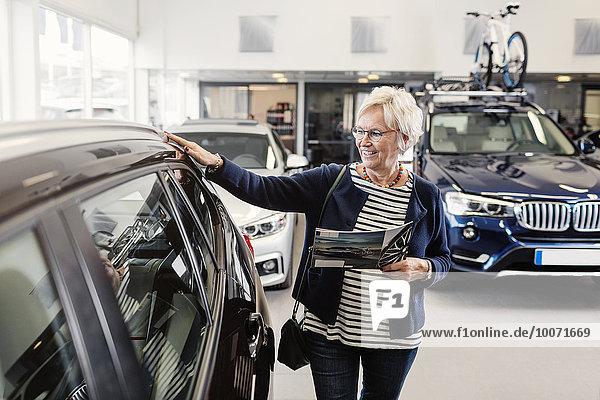 Seniorin untersucht Auto im Geschäft