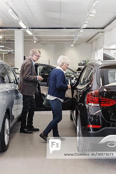 Seniorenpaar untersucht Auto im Geschäft