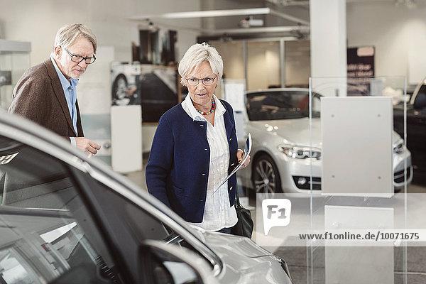 Seniorenpaar beim Betrachten des Autos im Ausstellungsraum