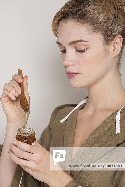 Schöne Frau mit Honigglas
