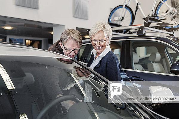 Glückliches Senior-Paar bei der Autoprüfung im Showroom