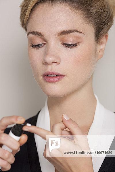 Frau spritzt Feuchtigkeitscreme auf ihren Finger