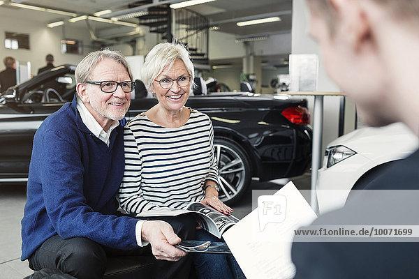 Glückliches Senior-Paar beim Anblick des Verkäufers im Autohaus