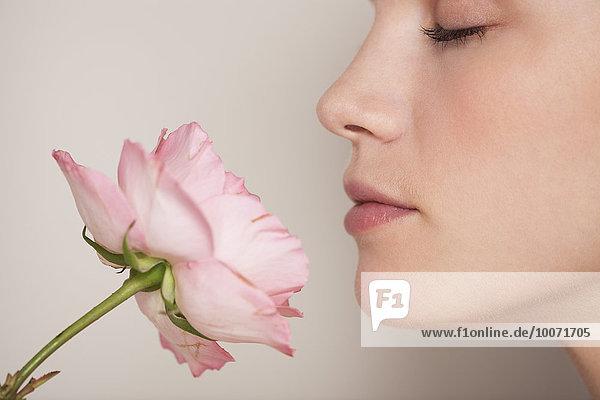 Schöne Frau  die eine Blume riecht.