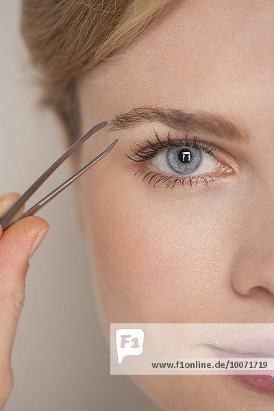 Schöne Frau zupft Augenbraue mit Pinzette