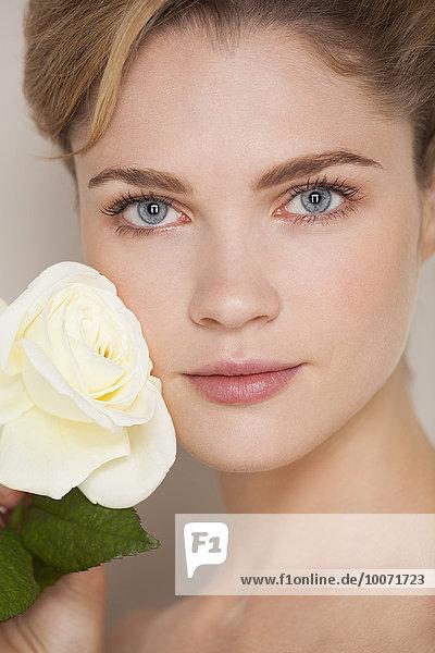 Schöne Frau  die Rose auf ihrem Gesicht berührt.