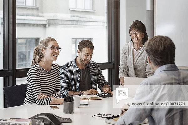 Glückliche Senior-Geschäftsfrau im Gespräch mit Kollegen im Vorstandszimmer