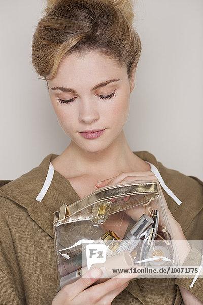 Frau schaut auf die Kosmetiktasche