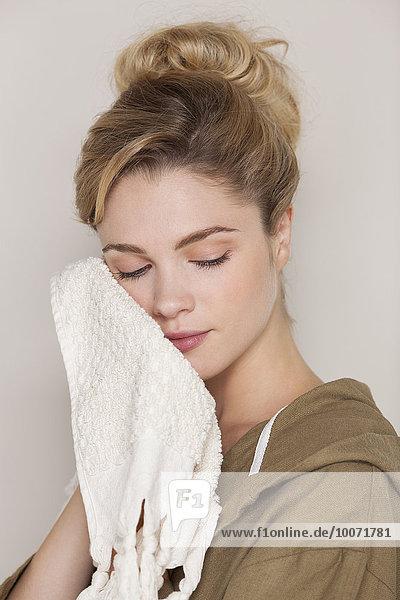 Schöne Frau  die ihr Gesicht mit einem Handtuch putzt.