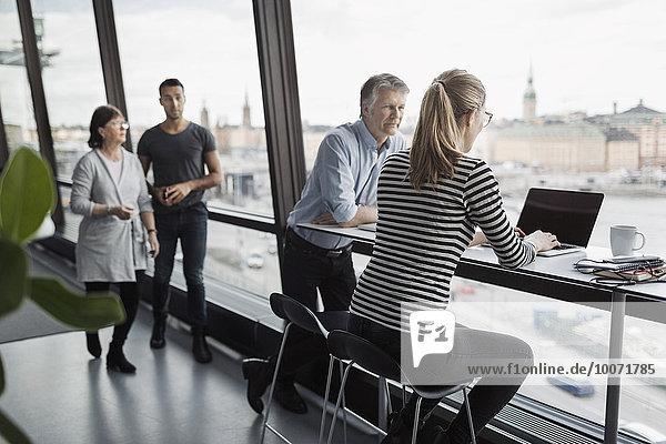 Geschäftsleute diskutieren am Fenster im Büro