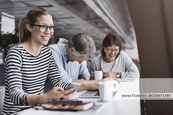 Zufriedene Geschäftsleute am Schalter im Büro
